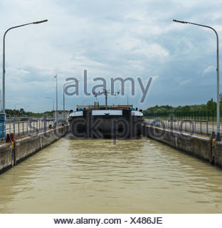Container ship in barrage with lock on river - Stock Photo