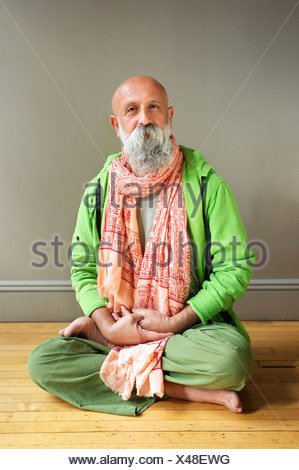 Portrait of mature man sitting in lotus pose on floor - Stock Photo