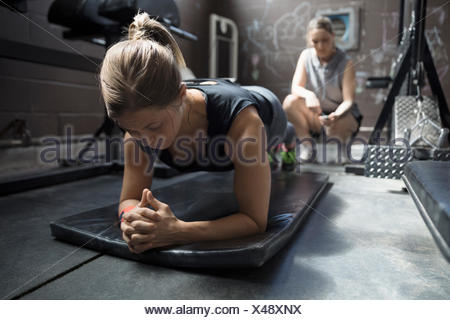 Personal trainer timing female client doing plank exercise in gritty gym - Stock Photo