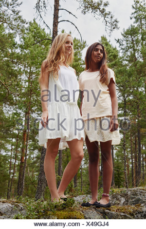 Portrait of teenage girls standing on rocks in forest - Stock Photo