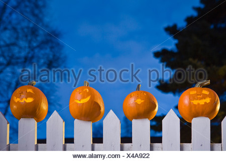 Jack-O-Lantern Faces Stuck On Top Of The Fence Boards Of White Picktet Fence At Twilight During Fall In Anchorage, Alaska. - Stock Photo
