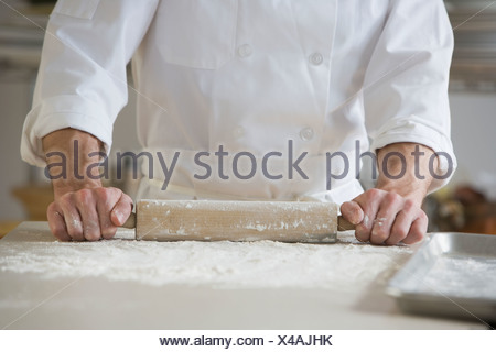 Pastry chef rolling out dough - Stock Photo