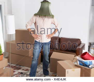 Man with lamp shade on head in home with cardboard boxes - Stock Photo
