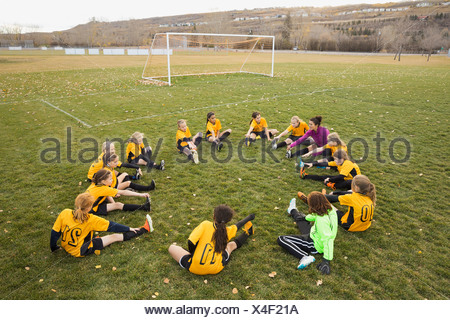 Coach and soccer team stretching on field - Stock Photo