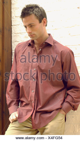 Semi profile of male short brown hair wearing dark red shirt open at neck chinos one hand in pocket other hand on hip standing - Stock Photo
