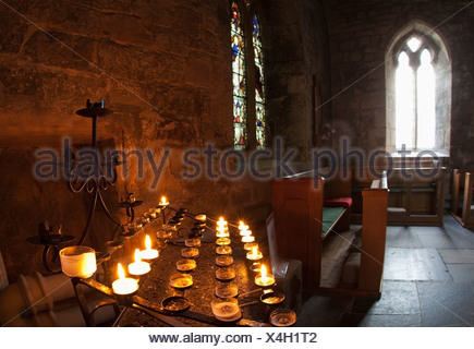 Candles Lit Inside A Church Sanctuary; Bamburgh, Northumberland, England - Stock Photo
