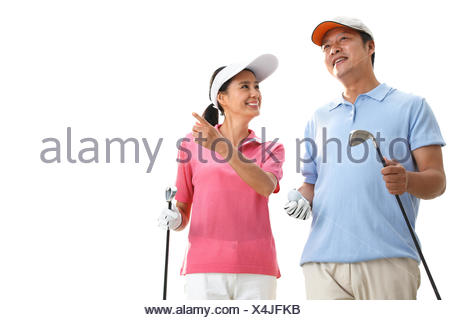 A middle-aged couple playing golf - Stock Photo