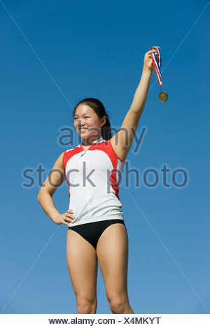 Female athlete being honored on podium, holding up medal - Stock Photo