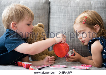Brother (2-3) and sister (2-3) having tea party with teddy bear - Stock Photo
