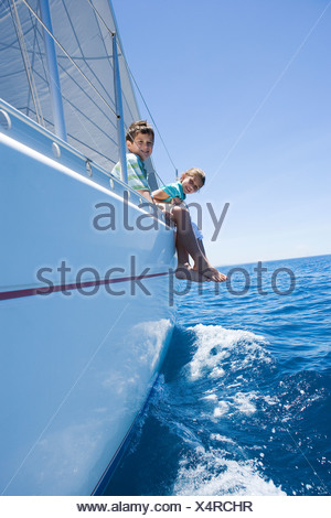Boy and girl  sitting on deck of sailing boat out to sea, feet dangling over side, smiling, side view, portrait tilt - Stock Photo