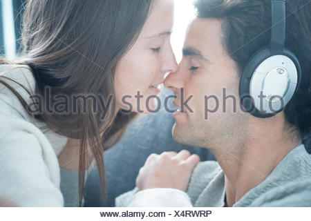 Young woman kissing man wearing headphones at home - Stock Photo