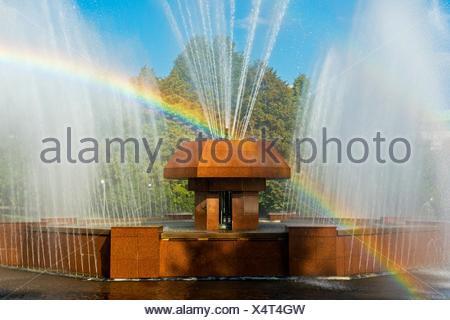Rainbow in the waterdrops of a fountain, Almaty, Kazakhstan. - Stock Photo