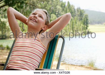 Girl (7-9) by lake, leaning back on deck chair. - Stock Photo