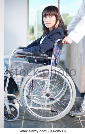 Woman in wheelchair assisted by male nurse - Stock Photo