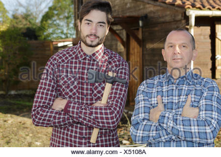 two friends lumberjacks in the forest with an axe - Stock Photo
