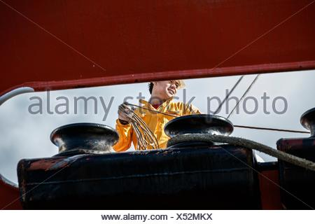 Worker fastening ropes to mooring posts on board oil tanker - Stock Photo