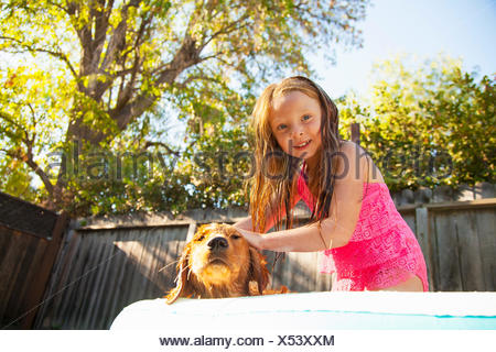 Portrait of girl petting dog in garden paddling pool - Stock Photo