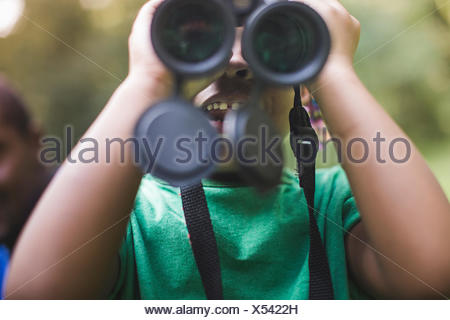 Close up of girl looking through binoculars in forest eco camp - Stock Photo