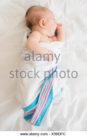 Baby girl (2-5 months) sleeping on bed - Stock Photo