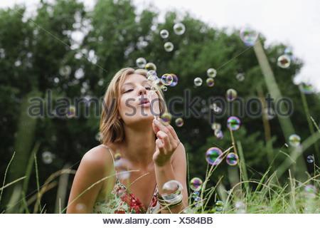 Woman blowing bubbles in field - Stock Photo