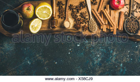 Ingredients for making mulled wine. Wine in glass bottle, honey, lemon, apples and spices on wooden board over old blue painted - Stock Photo