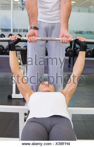 Trainer helping woman with lifting barbell in gym - Stock Photo