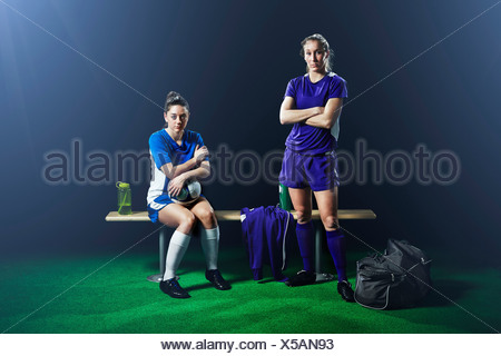 Portrait of two female soccer players on bench - Stock Photo