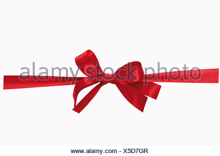 Red bow against white background, close-up - Stock Photo