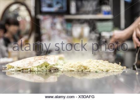 cooking of okonomiyaki - Stock Photo
