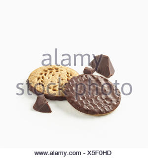 Chocolate covered cookies with pieces of chocolate on a white background; Toronto, Ontario, Canada - Stock Photo