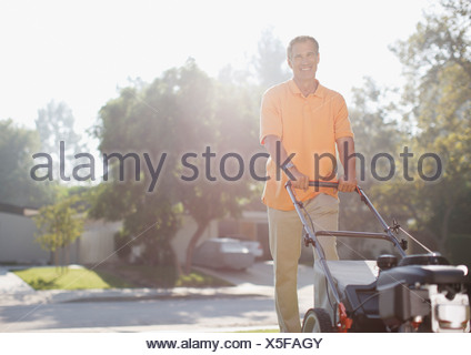 Older man mowing front lawn - Stock Photo