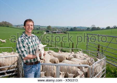 Portrait of shepherd holding lamb in pasture - Stock Photo