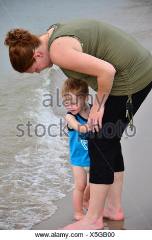 A young boy walks with his pregnant mother in lakeside surf. - Stock Photo