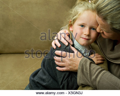 A young girl being hugged by her mum - Stock Photo