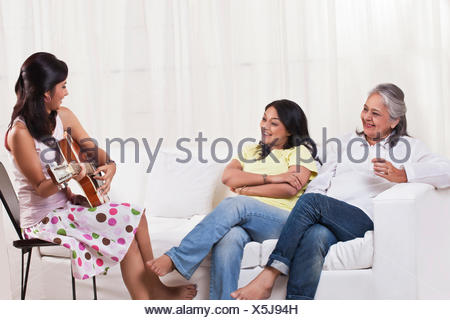Beautiful teenage girl playing guitar for her mother and grandmother - Stock Photo