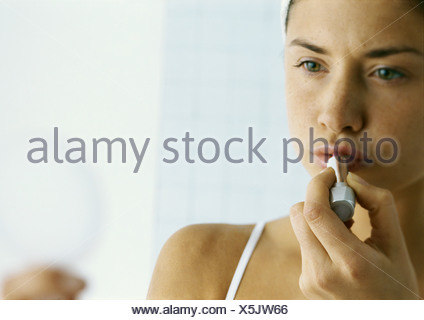 Young woman applying lipstick, close-up - Stock Photo