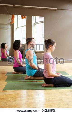 People kneeling in yoga class - Stock Photo