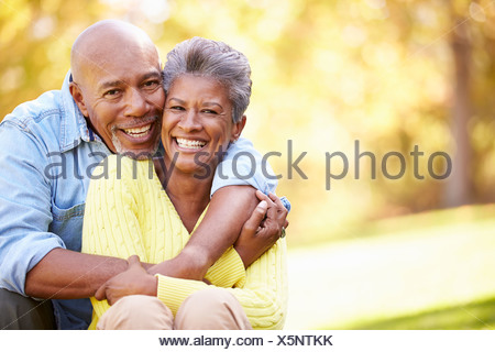 Senior Couple Relaxing In Autumn Landscape - Stock Photo