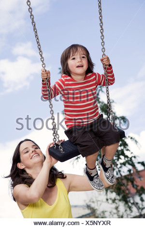 Germany, Berlin, Mother and son (3-4) at playground on swing, portrait, close-up - Stock Photo