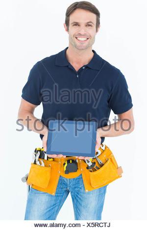 Happy carpenter holding digital tablet - Stock Photo