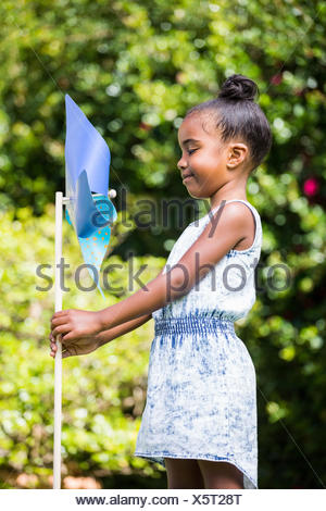 Little girl holding a pinwheel at park - Stock Photo