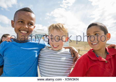 Boys standing outside with arms around each other - Stock Photo