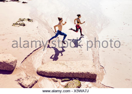 Young man and woman running along beach, elevated view - Stock Photo