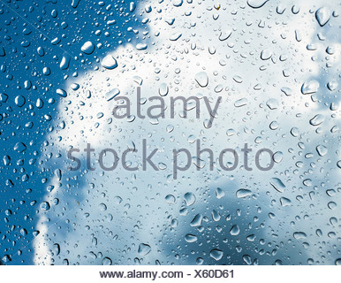 Raindrops on a window in front of storm clouds - Stock Photo