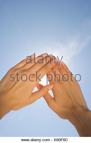 Close up of woman s hands blocking sun - Stock Photo