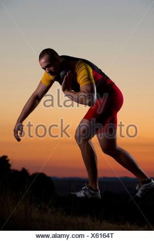 Young man preparing to throw shot put at sunset - Stock Photo