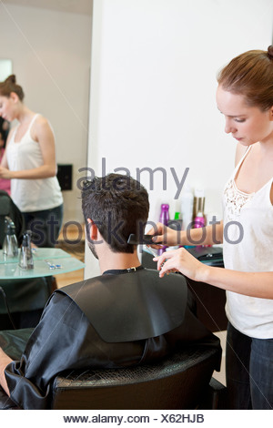 A female hairdresser cutting his male clients hair with scissors - Stock Photo