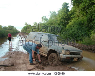 Digging out a car stuck in the mud on a road in the Gran Chaco, Paraguay - Stock Photo
