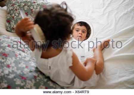 Girl (2-3) combing hair on bed with mirror - Stock Photo