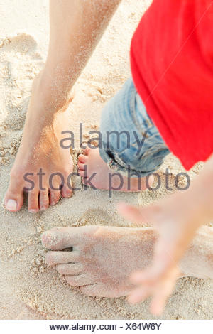 Cropped shot of legs of mother, father, and son (12-17 months) standing barefoot on sand - Stock Photo